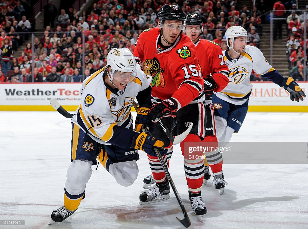 Craig Smith #15 of the Nashville Predators and Artem Anisimov #15 of the Chicago Blackhawks get physical during the NHL game at the United Center on February 25, 2016 in Chicago, Illinois.