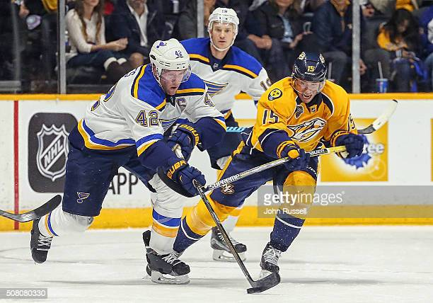 Craig Smith of the Nashville Predators battles for the puck against David Backes of the St Louis Blues during an NHL game at Bridgestone Arena on...