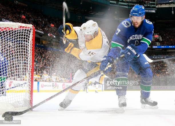 Craig Smith of the Nashville Predators checks Josh Leivo of the Vancouver Canucks during their NHL game at Rogers Arena December 6, 2018 in...