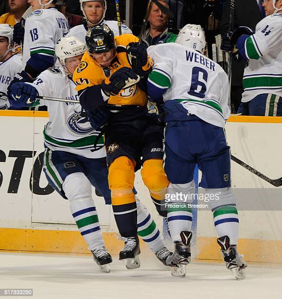 Craig Smith of the Nashville Predators collides with Yannick Weber of the Vancouver Canucks during the first period at Bridgestone Arena on March 24...