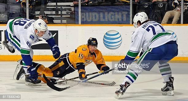 Craig Smith of the Nashville Predators falls between Nikita Tryamkin and Ben Hutton of the Vancouver Canucks during the first period at Bridgestone...