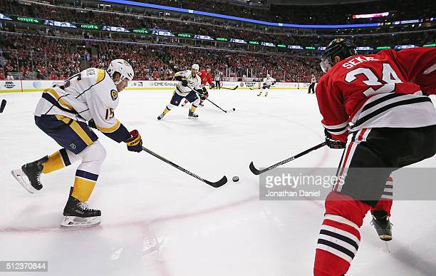 Craig Smith of the Nashville Predators knocks the puck away from Jiri Sekac of the Chicago Blackhawks at the United Center on February 25 2016 in...