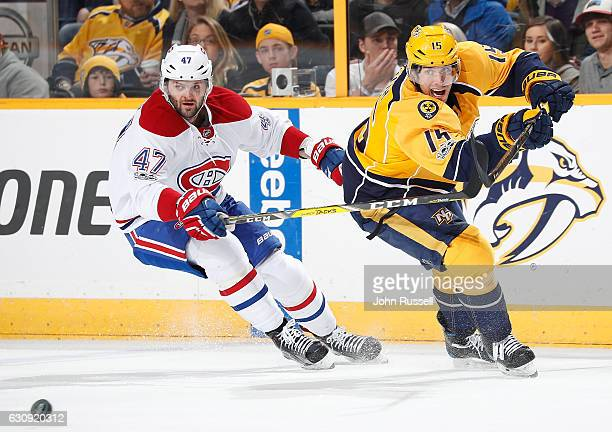 Craig Smith of the Nashville Predators passes the puck against Alexander Radulov of the Montreal Canadiens during an NHL game at Bridgestone Arena on...