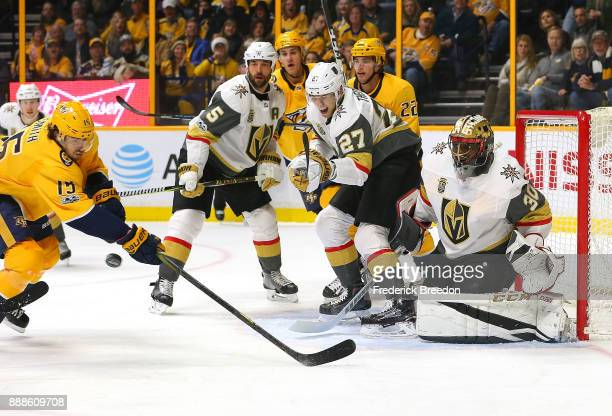 Craig Smith of the Nashville Predators swings at a bouncing puck in front of Deryk Engelland Shea Theodore and goalie Malcolm Subban of the Las Vegas...