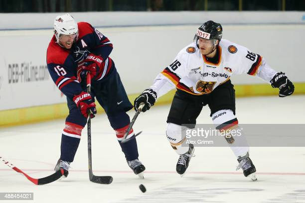 Craig Smith of USA is challenged by Daniel Pietta of Germany during the international ice hockey friendly match between Germany and USA at Arena...
