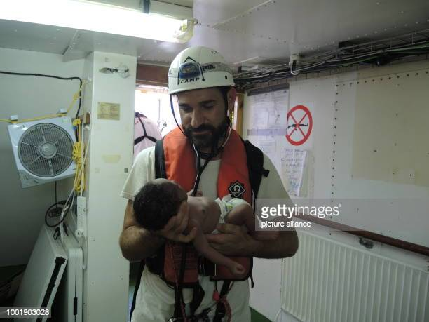 Craig Spencer a doctor with Doctors without Borders with a migrant child rescued from the Mediterranean on board the Aquarius a boat belonging to the...