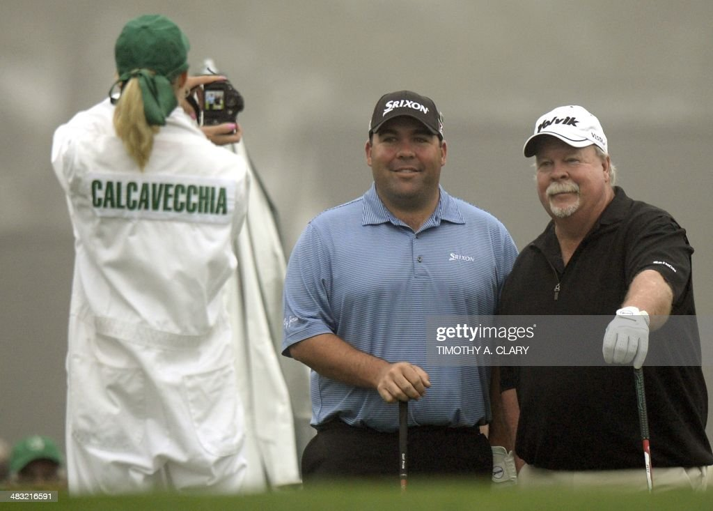 Craig Stadler and his son Kevin Stadler(C) from the US, pose for Mark Calcavecchia's caddie during a practice round April 7, 2014 at Augusta National Golf Club in Augusta, Georgia as they prepare for the 2014 Masters Golf Tournament. AFP PHOTO / Timothy A. CLARY / AFP PHOTO / Timothy A. CLARY