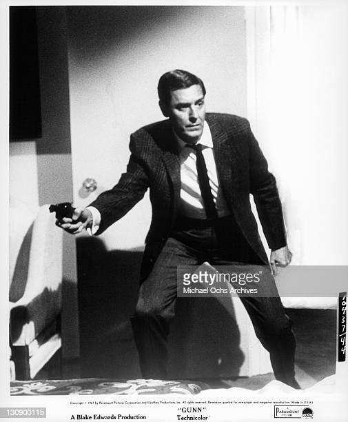 Craig Stevens walks into room while holding gun in a scene from the film 'Gunn' 1967