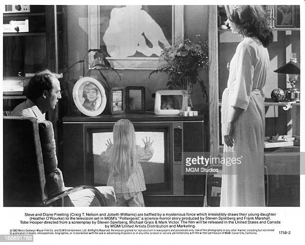 Craig T Nelson watches Heather O'Rourke approach the television with JoBeth Williams in a scene from the film 'Poltergeist', 1982.