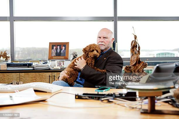 J Craig Venter poses for a portrait with his poodle Darwin at his oak desk in his office
