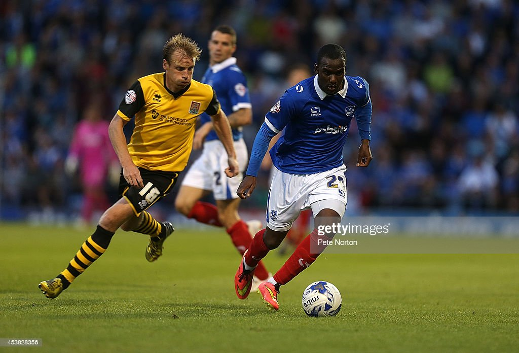 Craig Westcarr of Portsmouth moves forward with the ball away from Ricky Ravenhill of Northampton Town during the Sky Bet League Two match between Portsmouth and Northampton Town at Fratton Park on August 19, 2014 in Portsmouth, England.