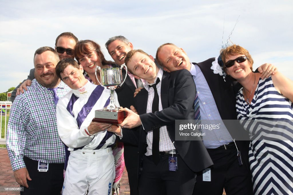 Craig Williams and winning connections all lean the same way as the trophy after winning the Herald Sun Carlyon Cup during Melbourne Racing at Caulfield Racecourse on February 9, 2013 in Melbourne, Australia.
