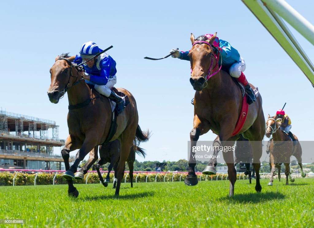 Craig Williams riding Crossing The Abbey (r) defeats Damien Oliver riding Khulaasa in Race 1, during Melbourne Racing at Flemington Racecourse on January 1, 2018 in Melbourne, Australia.