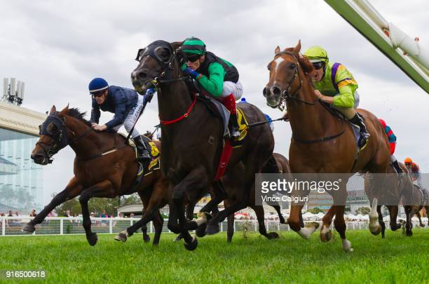 Craig Williams riding Super Cash defeats Damian Lane riding Flamberge and Mark Zahra riding Merchant Navy in Race 6 Rubiton Stakes during Melbourne...
