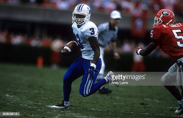 Craig Yeast of the Kentucky Wildcats runs with the ball as Ronald Bailey of the Georgia Bulldogs goes for the tackle on October 27 1997 at Sanford...