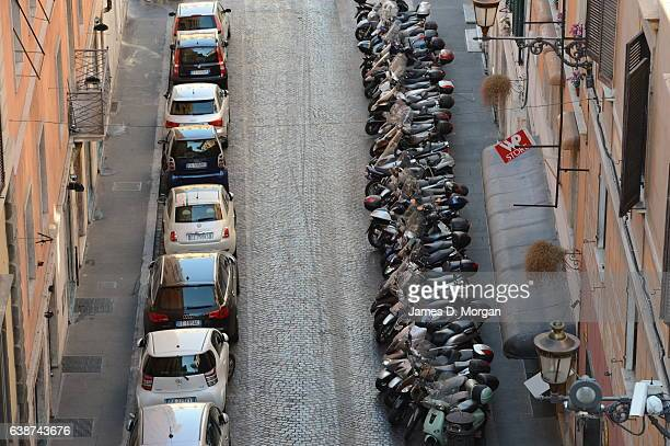 Crammed Parking in Italy showing Multiple smart cars on one side and an endless line of Scooters on the other on August 30 2012 in Rome Italy