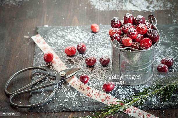 cranberries in small zinc bucket, icing, scissor and ribbon on slate, wood - icing sugar stock pictures, royalty-free photos & images