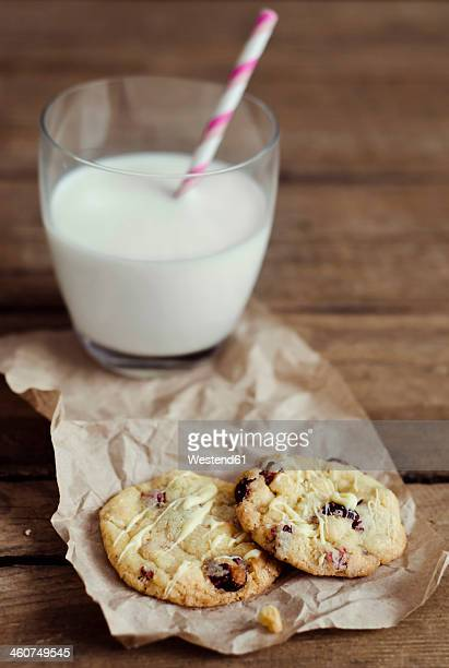 Cranberry cookies with glass of milk on wooden table, close up