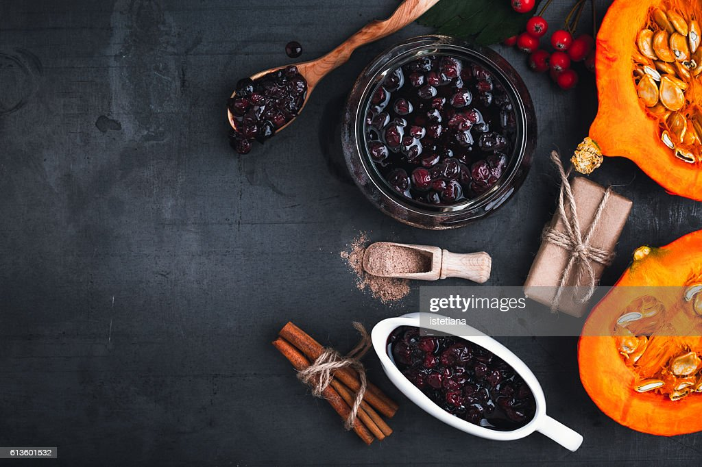 Cranberry sauce,  halved fresh pumpkin and  cinnamon sticks on grey background with  copyspace for healthy seasonal autumn cuisine. Thanksgiving concept : Stock Photo