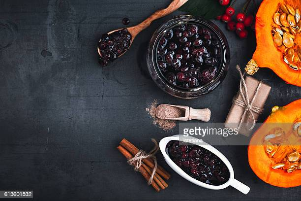 Cranberry sauce,  halved fresh pumpkin and  cinnamon sticks on grey background with  copyspace for healthy seasonal autumn cuisine. Thanksgiving concept