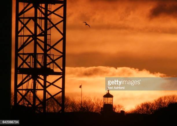 crane and lighthouse sunset - flagpole sitting stock photos and pictures