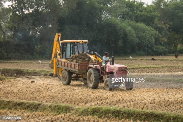 crane and tractor excavating earth in farmland - tiller stock photos and pictures