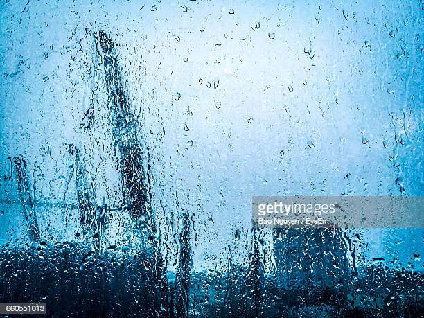 Crane At Construction Site Seen Through Wet Glass During Monsoon