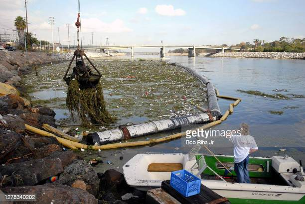 Crane bucket clears some of the estimated 150 tons of trash that has collected in the Los Angeles River after the season's first heavy rainfall over...