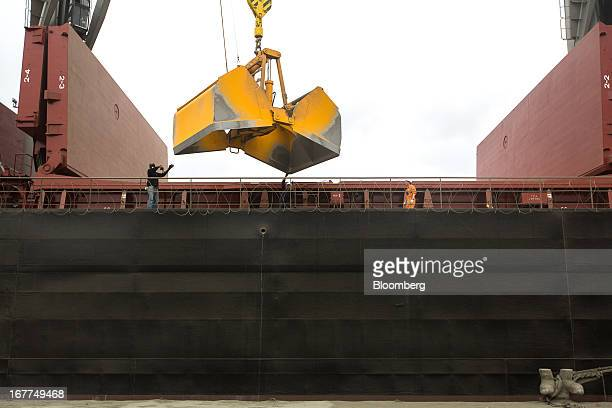 A crane bucket hovers of the hold of a bulk carrier ship as it unloads 'Clinker' while moored on the dockside at Mombasa port managed by the Kenya...