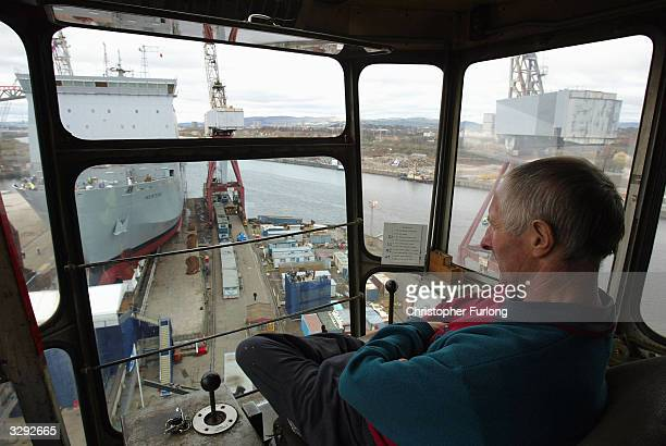 Crane driver Thomas Early looks on as Mounts Bay a newly constructed landing craft for the Royal Fleet Auxiliary slides down the slipway into the...