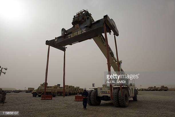 A crane is directed as US lorries are loaded up on July 23 at Contingency Operating Base Speicher on the outskirts of Tikrit 160 kilometres north of...