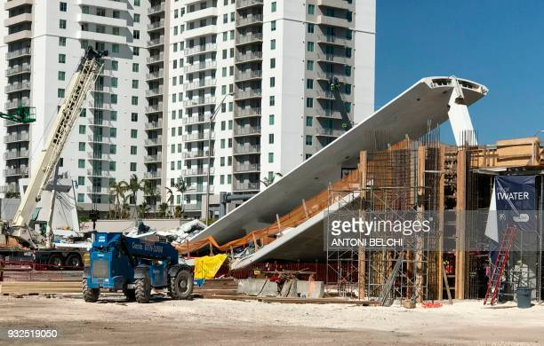 TOPSHOT A crane is seen near a newly installed pedestrian bridge that collapsed over a sixlane highway in Miami Florida on March 15 crushing a number...