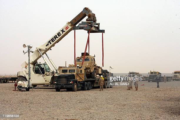 A crane is used to lift US military vehicles onto lorries on July 23 at Contingency Operating Base Speicher on the outskirts of Tikrit 160 kilometres...