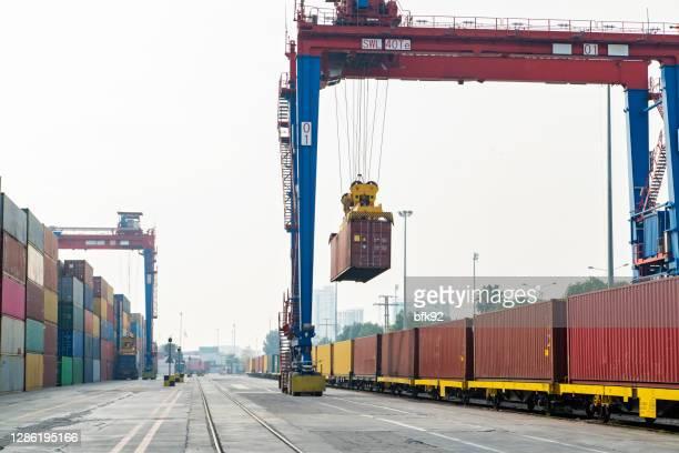 クレーンはコンテナを持ち上げ、貨物列車を積み込む。 - 貨物列車 ストックフォトと画像