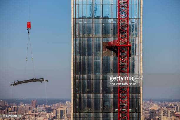 crane lifting on new york skyscapper with central park in the background - eric van den brulle stockfoto's en -beelden
