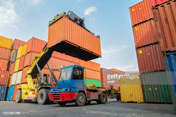 crane lifting up container in a port. - container stock pictures, royalty-free photos & images