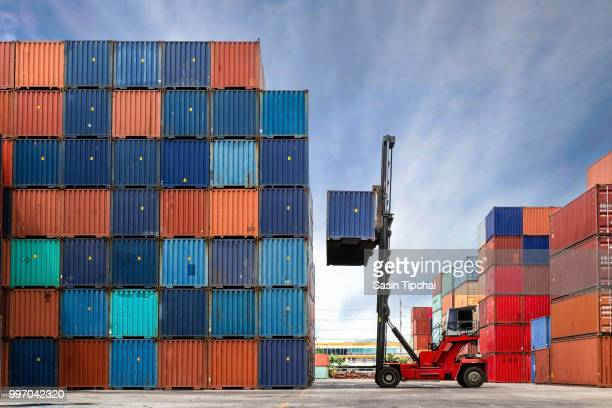 crane lifting up container in yard - heavy industry stock photos and pictures