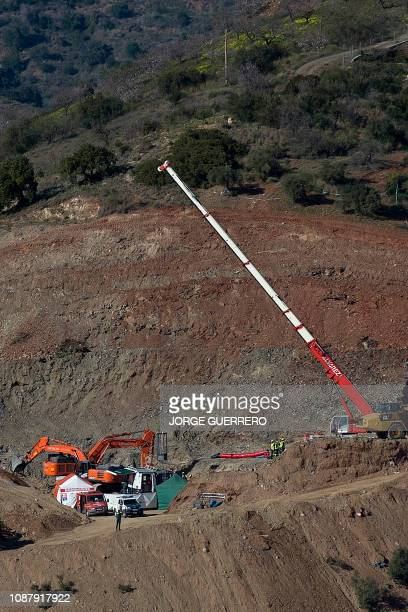 A crane lifts a cage that will be used to lower the miners who will go on with the manual rescue works at the site where a child fell down a well in...
