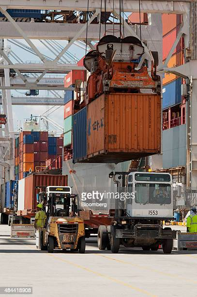 A crane lifts a container off a truck to be loaded onto a ship at the Port of Savannah in Savannah Georgia US on Friday Aug 14 2015 The trade deficit...