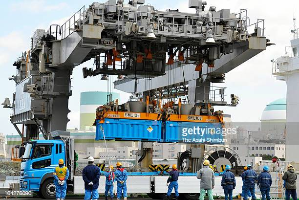 A crane lifts containers of radioactive waste and loads onto a cargo ship in Shikoku Electric Power Co Ikata Nuclear Power Plant on March 21 2013 in...