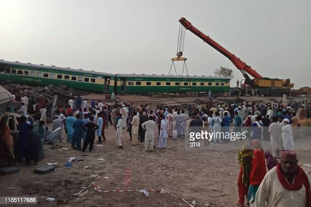 A crane lifts damaged carriages at the site where two trains collided in Rahim Yar Khan district of Punjab province on July 11 2019 At least 11...