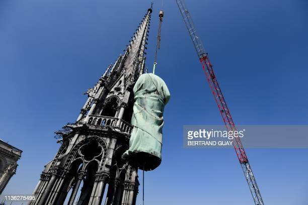 Crane lifts one of 16 copper statues, sitting 50 meters above the ground, off the Notre-Dame-de-Paris Cathedral to be taken for restoration on April...