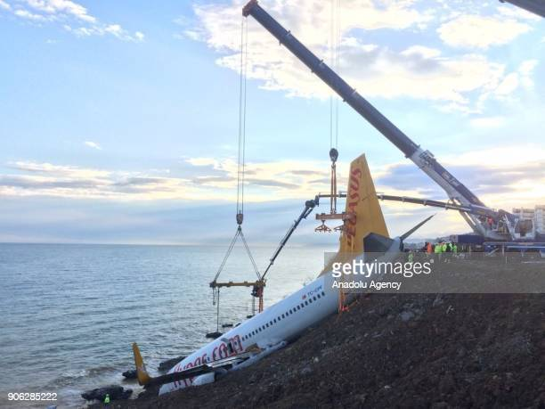 A crane lifts Pegasus airplane which was stucked in mud as it skidded off the runway after landing in Trabzon Airport Turkey early Sunday on January...