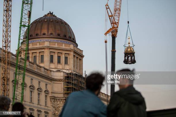 Crane lifts the newly-finished gold-covered cupola and cross onto the dome of the rebuilt Berlin City Palace on May 29, 2020 in Berlin, Germany. The...
