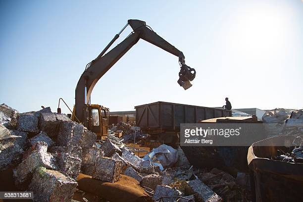 Crane loading metal blocks in scrap yard