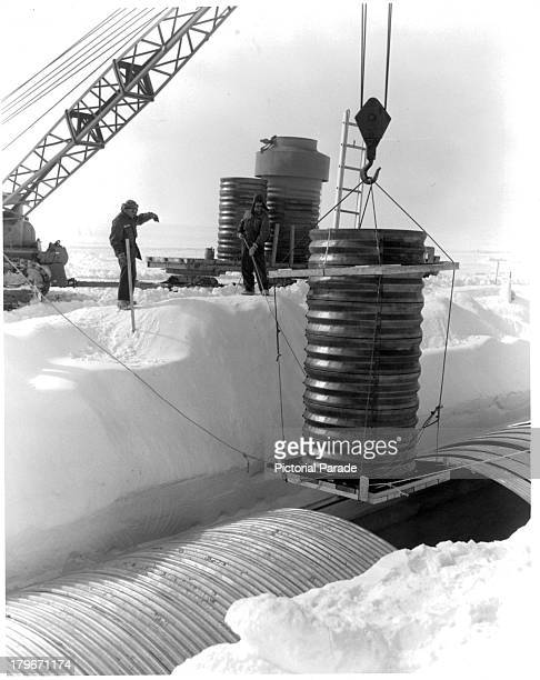 A crane lowers a hatch into a lateral trench of the permanent camp at Camp Century in Greenland