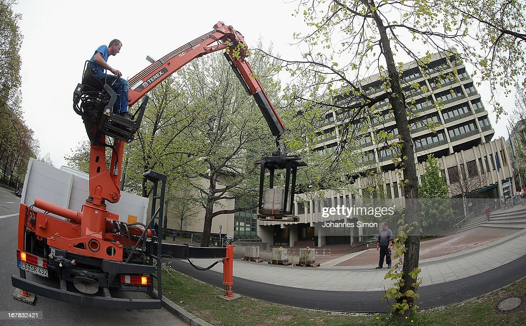 A crane lowers concrete barricades around the Oberlandgericht Muenchen state courthouse a week before the NSU trial on April 30, 2013 in Munich, Germany. Security will be high around the trial, in which Beate Zschaepe, the only surviving member of the NSU neo-Nazi murder trio, and four accused NSU supporters will face charges. The NSU trio murdered at least nine immigrants and one policewoman between 2000 and 2007.