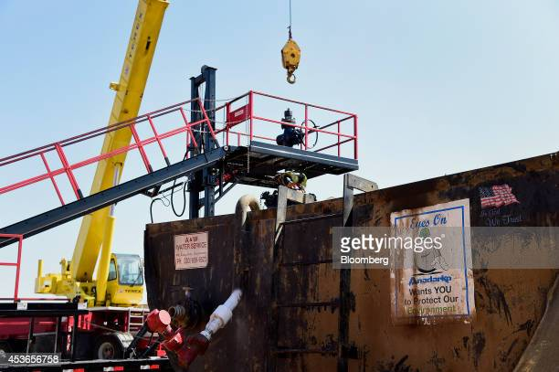 A crane lowers equipment at an Anadarko Petroleum Corp hydraulic fracturing site north of Dacono Colorado US on Tuesday Aug 12 2014 US crude oil...