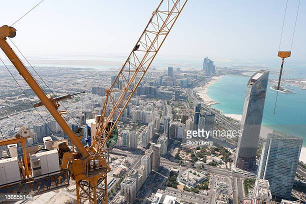 A crane operates above a Central Market residential tower an Aldar PJSC project under construction in Abu Dhabi United Arab Emirates on Wednesday Jan...