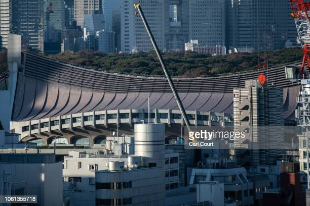 A crane operates next to the curved roof of Yoyogi National Stadium on November 14 2018 in Tokyo Japan The 13291 seat stadium is set to host handball...